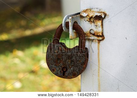 padlock hanging on a white wall and a yellow background