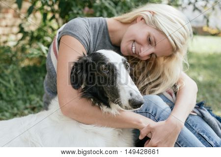 Happy woman and her dog posing outdoor