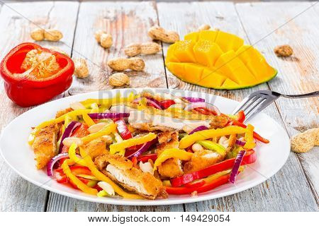 mango bread crumbed chicken meat peanuts bell pepper red onion salad on white dish with half of mango cutting in cubes close-up