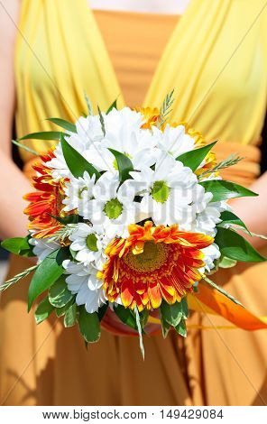Summer bouquet in hands of the bride in a bright orange dress. Decoration of flowers in their hair hairstyle. Hippie Bride. Sunny mood.
