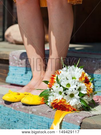 Feet girl in yellow ballet flats and bridal bouquet. Decoration of flowers in their hair hairstyle. Hippie Bride. Sunny mood.