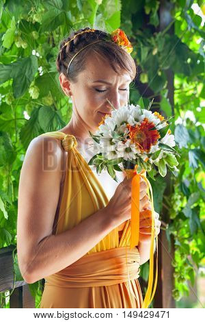 Young beautiful girl bride in a bright orange dress in the Russian wooden house. Summer bouquet in hands of the bride. Decoration of flowers in their hair hairstyle. Hippie Bride. Sunny mood.