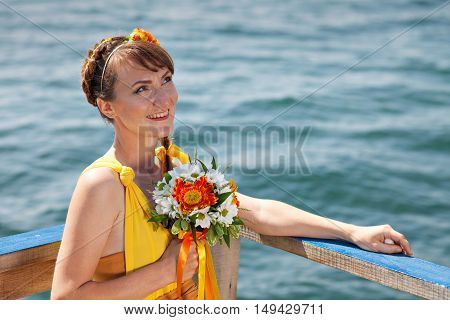 Young beautiful girl in the bright orange bride on a background of lake. Summer bouquet in hands of the bride. Decoration of flowers in their hair hairstyle. Hippie Bride on the shore of Lake Baikal.