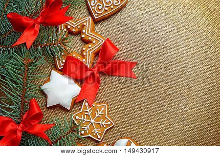 Delicious cookies with Christmas decoration on golden background