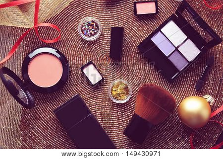 Colorful makeup cosmetic with Christmas decoration on golden beaded mat background