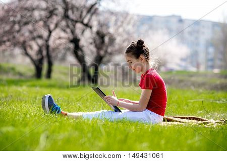 kid hold tablet phone for playing and education. Little girl Using a Tablet closeup. a girl with the tablet on the nature
