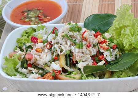 Spicy and sour mixed herb salad with crab is Thai cuisine as kaffir lime leaves,minced red chili,sliced shallots,parsley,lettuce and peppermint. Selective focus.