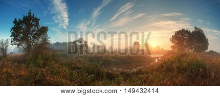 Sun Rising Over Meadow In Misty Autumn Morning