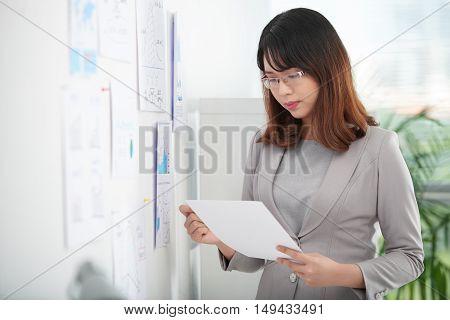 Portrait of Asian female entrepreneur reading business document