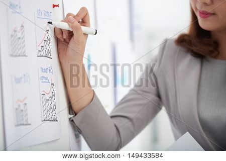 Business woman drawing arrow above increasing chart