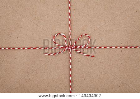 Christmas or New Year string or twine tied in a bow on kraft paper texture. Gift or present concept.