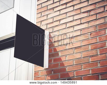 Signboard shop Mock up Black metal sign display on brick wall Building exterior