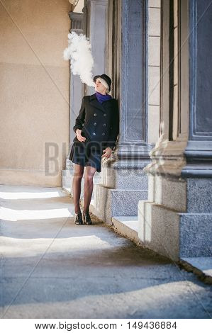 Portrait Of Young Beautiful Woman With White Hair, In A Black Coat, A Skirt And A Black Hat, Smoking