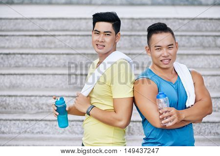 Portrait of two Asian fit friends with water bottles and towels
