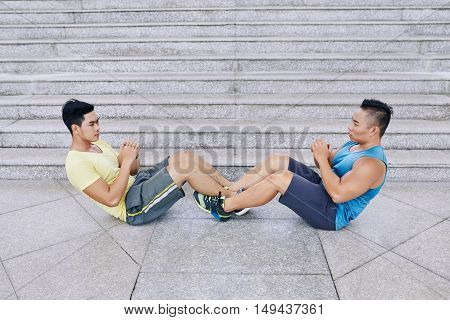 Two strong Vietnamese sportsmen doing sit-ups outdoors
