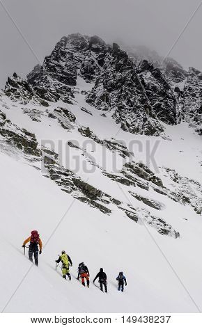 Group of climbers with ice axes traverses the snowy towards the high rock. Dark clouds. Bad weather. Mountaineering in High Tatras Slovakia