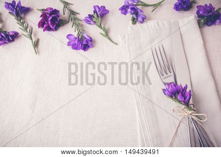 Purple flower table place setting on linen toning copy space background