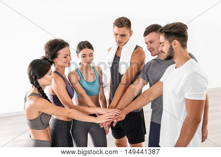 Team work concept. Group of people making pile of hands in gym