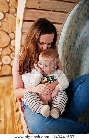Young Caucasian Mother And Her Baby Boy Sitting On Decorated Wooden Chair