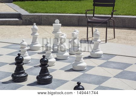 Black and white chessmen on the street chessboard in the daylight