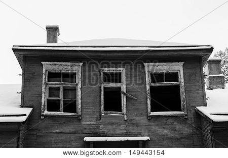 black and white photo of the old abandoned house in snow