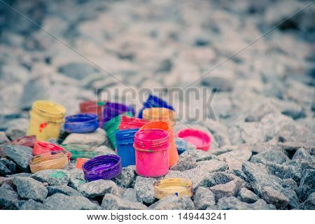 small jars from under paint of different colors on gray pebbles