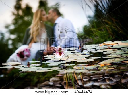 Kissing newlywed couple reflecting in lake - focus on waterlily