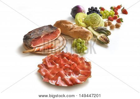 Snack of sliced Speck on dish with fruits vegetables and bread