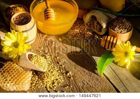 Apiary Products( Honeycombs ,honey, Pollen) And Flowers On A Wooden Table