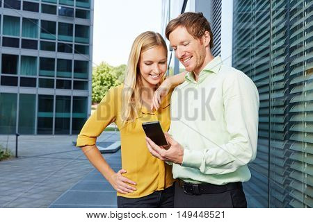 Man showing woman a website on a smartphone next to his office in the city