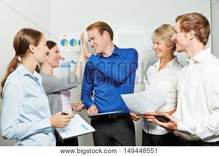 Cheering business people giving high five in the office for motivation