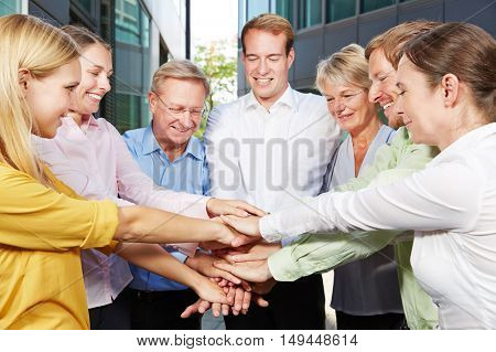 Many business people stacking their hands for motivation next to the office