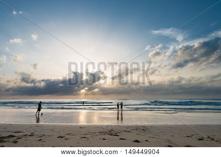 People Enjoy Tropical Sunset On The Beach