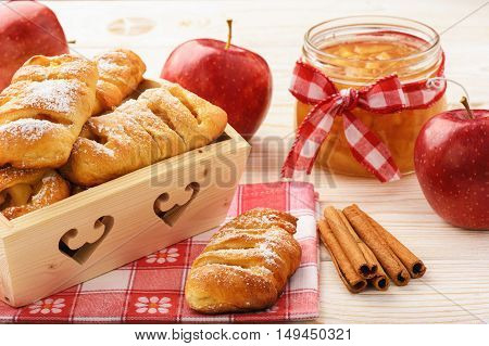 Fresh yeast buns with apple jam and cinnamon on white wooden background.