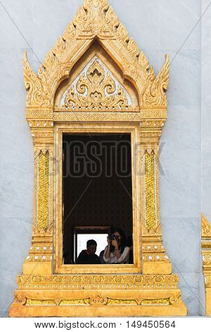 Tourist Snaps A Photo From An Ornate Window Of Wat Traimit, An Important Religious Site In Bangkok.