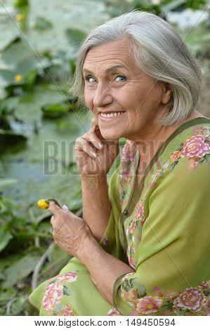 Elderly woman in a summer near lake