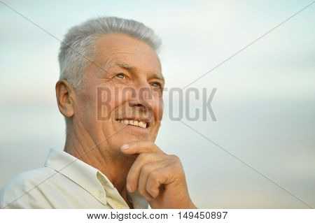 Portrait of an attractive older man on the background of the sky