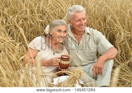 Senior couple resting at summer field with milk in jug