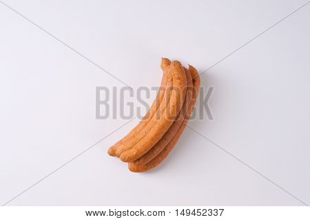 stack of long thin sausages on white background