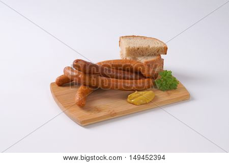 long thin sausages with slices of bread and mustard on wooden cutting board