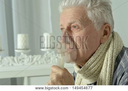 Portrait of elderly man with flu inhalation
