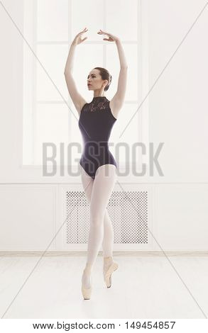 Classical Ballet dancer portrait. Beautiful graceful ballerine in black practice fifth ballet position near large window in light hall. Ballet class training, high-key soft toning. Vertical image