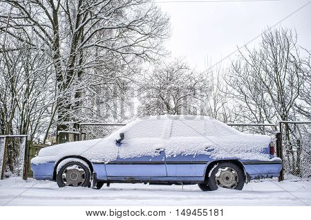 old rusty blue car covered with snow in winter