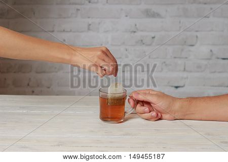 Men holding cup of tea and woman get him tea bag