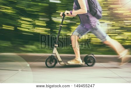 female rides a scooter at speed down the road blurred background the green trees
