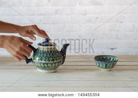 Girl's hand with traditional asian ceramic teapot