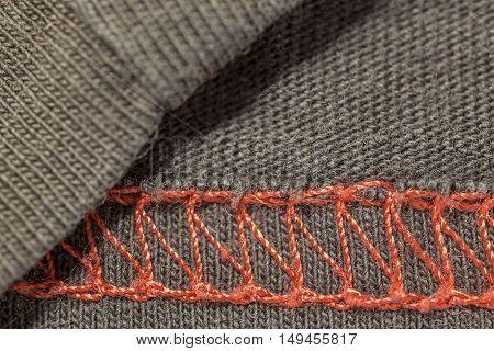 closeup macro red overlock seam on a brown T-shirt fabric