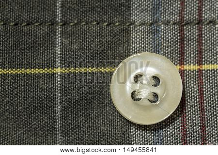 button fastened to the colorful tartan shirt