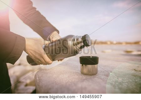 Man pours hot tea from a thermos into a cup which stands on an ice flow on the river bank in the spring sunny day