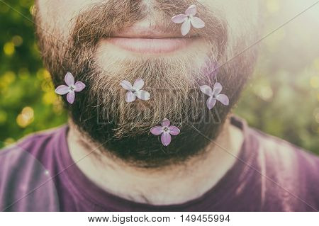 close-up of young happy man with lilac flowers in his beard against the background of juicy greenery